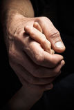 Mãos de um homem idoso que guarda a mão de um homem mais novo Fotografia de Stock Royalty Free