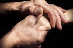 Mãos de um homem idoso que guarda a mão de um homem mais novo Imagens de Stock Royalty Free