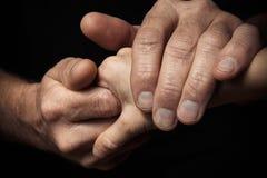 Mãos de um homem idoso que guarda a mão de um homem mais novo Fotos de Stock Royalty Free