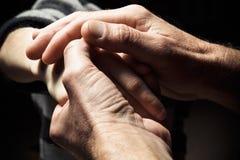 Mãos de um homem idoso que guarda a mão de um homem mais novo Imagem de Stock Royalty Free