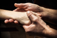 Mãos de um homem idoso que guarda a mão de um homem mais novo Imagens de Stock