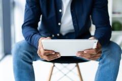Mãos de um homem de negócios africano que usa a tabuleta digital no escritório imagens de stock