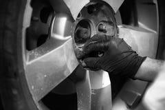 Mãos de um homem que aperta os parafusos em um pneu do veículo Fotografia de Stock Royalty Free