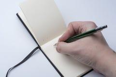 Mãos de um homem que guarda um caderno e uma pena em um fundo branco imagem de stock