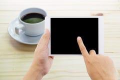 Mãos de um homem que guarda o dispositivo vazio da tabuleta fotos de stock