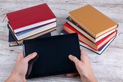 Mãos de um homem que guarda uma tabuleta ao lado de uma pilha de livros Vista de acima E Imagens de Stock Royalty Free