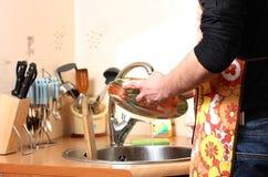 Mãos de um homem que lave pratos na cozinha imagem de stock