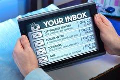 Mãos de um homem que olha email na tabuleta imagem de stock