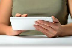 Mãos de um homem que usa uma tabuleta do PC, do baixo ângulo Fotografia de Stock
