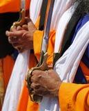 Mãos de um homem superior sikh que guardam a espada durante f religioso imagens de stock royalty free