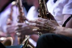 Mãos de um músico Jogadores de saxofone, concerto Close-up imagem de stock