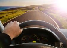 Mãos de um motorista On Steering Wheel de um carro fotos de stock royalty free