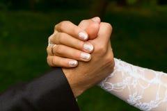 Mãos de um noivo e de uma noiva Fotos de Stock