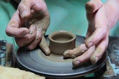 Mãos de um oleiro, criando um frasco de terra na roda da cerâmica imagem de stock royalty free