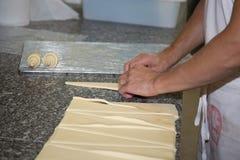 Mãos de um padeiro que faz croissant no fundo cinzento Imagem de Stock