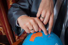 Mãos de um par novo no globo dos dedos Fotografia de Stock Royalty Free