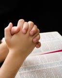 Mãos de uma criança abraçada na oração fotos de stock