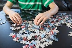 Mãos de uma criança que faz um enigma Fotografia de Stock