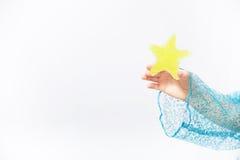 Mãos de uma criança que guarda a estrela pequena Fotografia de Stock