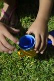 Mãos de uma criança que joga com copos plásticos foto de stock