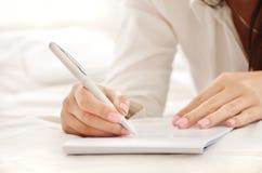 Mãos de uma escrita bonita da mulher nova em uma almofada Imagens de Stock