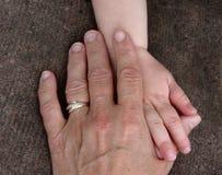 Mãos de uma jovem criança e de um toque superior velho Imagens de Stock