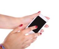 Mãos de uma jovem mulher e de um telefone celular Fotos de Stock Royalty Free