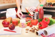 Mãos de uma jovem mulher que prepara a caixa de almoço escolar Imagem de Stock