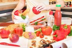 Mãos de uma jovem mulher que prepara a caixa de almoço escolar Imagens de Stock Royalty Free