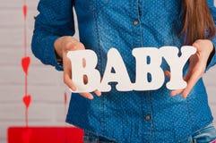 Mãos de uma menina com bebê da palavra Imagem de Stock Royalty Free