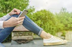 Mãos de uma menina com um telefone celular Foto de Stock Royalty Free