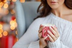 Mãos de uma menina do close-up que guarda um copo com marshmallow e cocos foto de stock royalty free