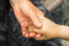 Mãos de uma menina e de uma avó idosa Mãos das crianças que guardam o homem idoso, conceito do dia da bondade do mundo foto de stock
