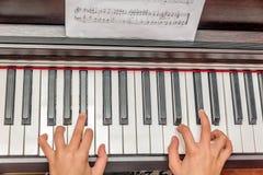 Mãos de uma menina que joga o piano Fotografia de Stock