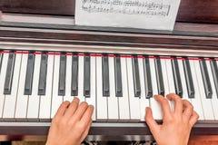 Mãos de uma menina que joga o piano Imagens de Stock Royalty Free