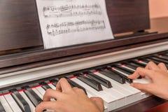 Mãos de uma menina que joga o piano Foto de Stock