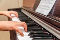 Mãos de uma menina que joga o piano Imagem de Stock