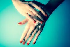 Mãos de uma moça com pregos vermelhos e de gotas do creme Close-up em um fundo azul Vintage, foto retro do estilo do grunge imagem de stock