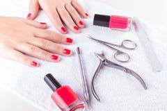 Mãos de uma moça perto das ferramentas do tratamento de mãos em uma toalha branca fotos de stock