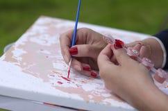 Mãos de uma moça que pinte uma imagem Fotos de Stock