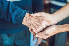 Mãos de uma mulher adulta e de um homem novo Inquietação com as pessoas idosas C Fotografia de Stock Royalty Free