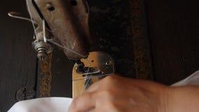 Mãos de uma mulher adulta que rabisca o pano branco em uma máquina de costura manual velha Processamento dobro da borda da tela d filme