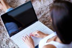 Mãos de uma mulher que datilografa em um laptop Fotografia de Stock Royalty Free
