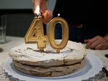 Mãos de uma mulher que ilumina velas douradas quatro e zero de um bolo de aniversário que comemora 40th imagens de stock