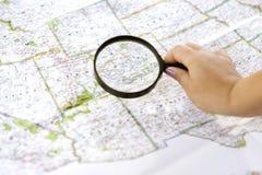 Mãos de uma mulher que usa uma lupa em um mapa do Estados Unidos imagens de stock