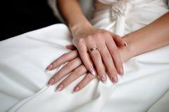 Mãos de uma noiva com uma aliança de casamento Fotos de Stock Royalty Free