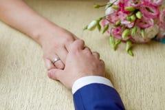 Mãos de uma noiva e de um noivo, apenas casadas, um bouque nupcial Imagens de Stock Royalty Free