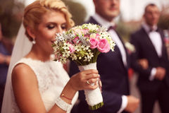 Mãos de uma noiva que guarda seu ramalhete do casamento Fotografia de Stock Royalty Free