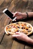 Mãos de uma pizza pedindo da mulher com um dispositivo sobre uma tabela de madeira do espaço de trabalho Todos os gráficos da tel fotos de stock