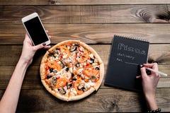 Mãos de uma pizza pedindo da mulher com um dispositivo sobre uma tabela de madeira do espaço de trabalho Todos os gráficos da tel imagem de stock royalty free